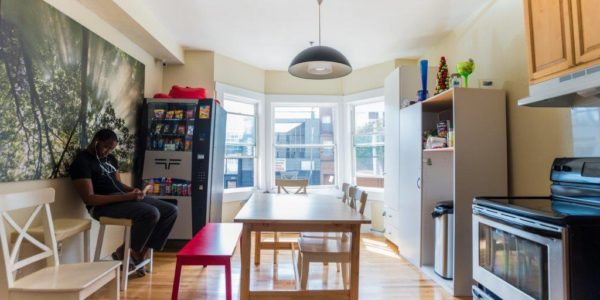 Man sitting in the common kitchen area of 221 7th street coliving residences and listening to the music through earphones. Kitchen has dining table and chairs, bench, stove, oven, cabinets, and shelf unit.