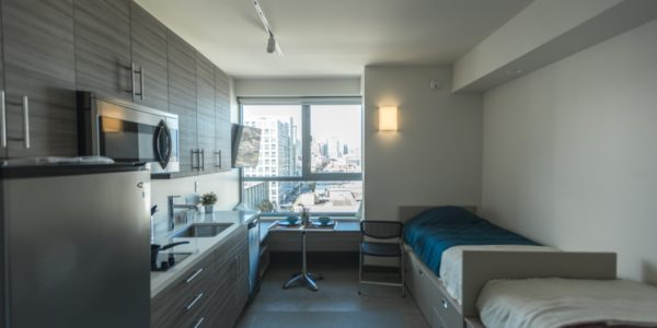 Modern double bedroom furnished with two beds, full-size kitchen, and dining set. Room is filled with sunlight and has beautiful view of San Francisco SoMa district.