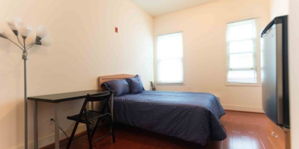 Furnished single bedroom in 556 Green Cohousing community includes full-size bed, desk, chair, lamp, refrigerator, and closet. Room is filled with sunlight and has a great view.
